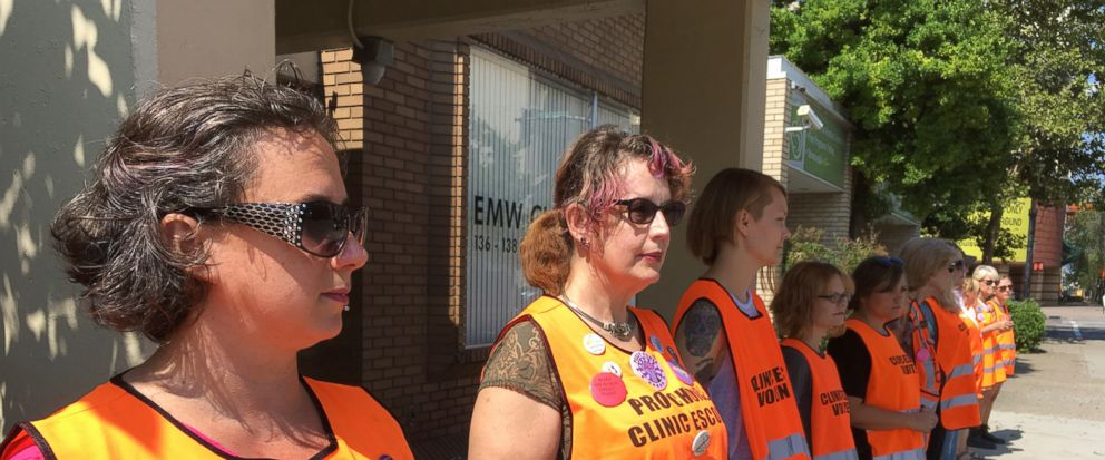 "In this Monday, July 17, 2017 photo, Meg Stern, left, and other escort volunteers lined up outside the EMW Womens Surgical Center in Louisville, Ky. A federal judge issued an order Friday, July 21, 2017, to keep protesters away from a ""buffer zone"""