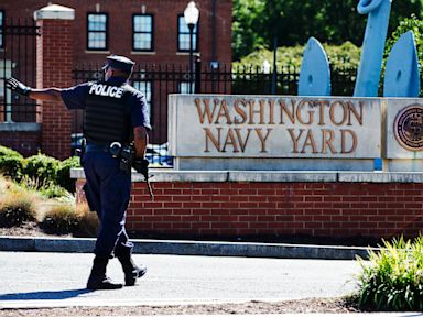 PHOTO: An armed officer who said he is with the Department of Defense, warns a vehicle to stay away from the gate at the Washington Navy Yard in Washington, on Sept. 17, 2013