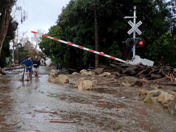 PHOTO: People walk through a crossing for the main line of the Union Pacific Railroad blocked with debris from mudslides following heavy rains in Montecito, California, January 9, 2018.