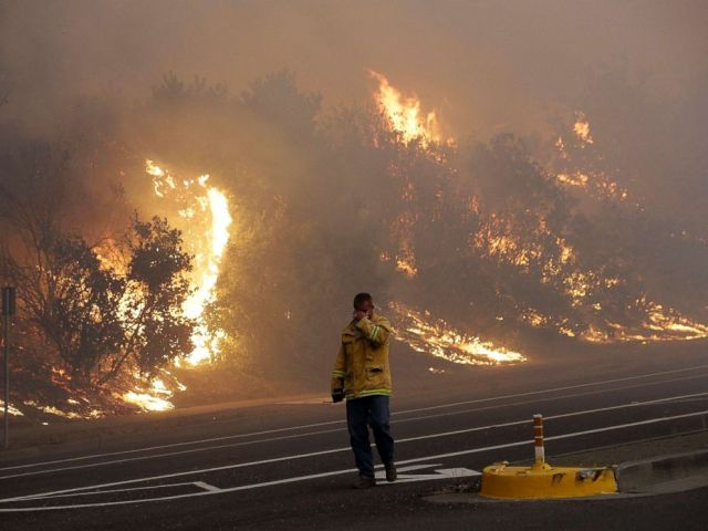 PHOTO: A firefighter covers his eyes as he walks past a burning hillside in Santa Rosa, Calif., Oct. 9, 2017.