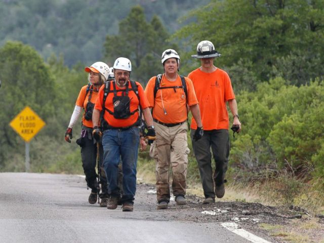 PHOTO: Members of the Tonto Rim Search and Rescue team walk back to the Gila County Sheriffs Office mobile command center after searching along the banks of the East Verde River, July 16, 2017, in Payson, Ariz.