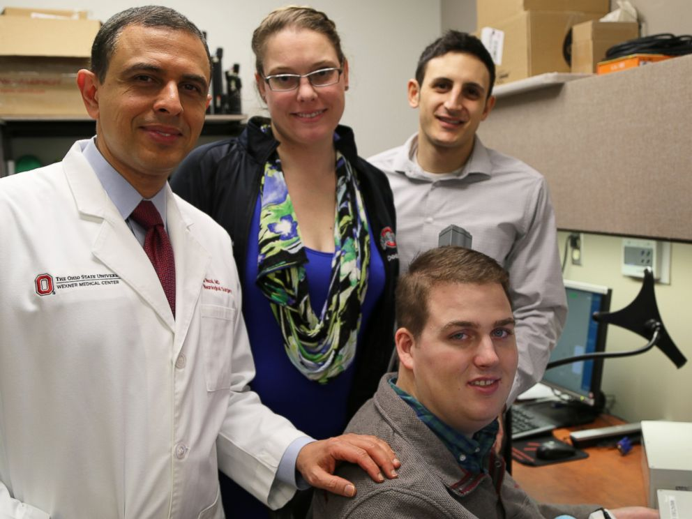 PHOTO: Patient Ian Burkhart, seated, poses with members of the research team. from left, Dr. Ali Rezai and Dr. Marcie Bockbrader of The Ohio State University Wexner Medical Center and Nick Annetta of Battelle during a neural bypass training session.