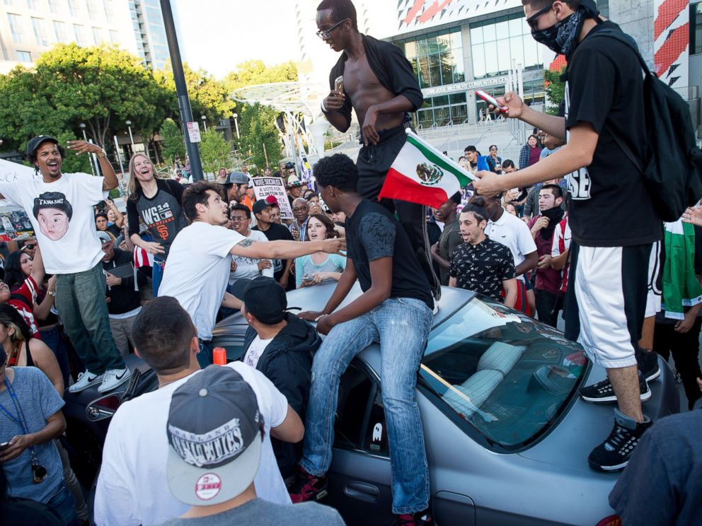 PHOTO: Protesters against GOP presidential candidate Donald Trump climb on a car outside a Trump campaign rally on Thursday, June 2, 2016, in San Jose, Calif.