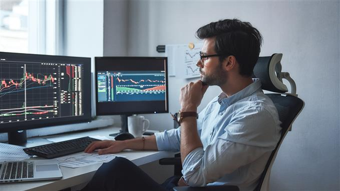 Trader analyzing charts on screen