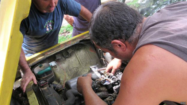 Un grupo de hombres tratan de reparar el carburador de un Lada.