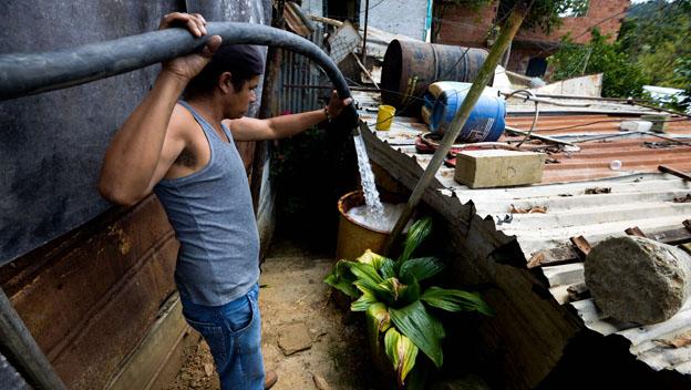 Hombre se abastece de agua en Caracas