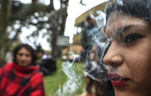 """An activist smokes a joint during a protest in Bogota, Colombia under the motto """"No vamos a pagar, lo vamos a pegar"""" ('We are not going to pay for it, we are going to get the kick out of it""""). She and others were protesting against fines for smoking marijuana on August 1, 2017."""