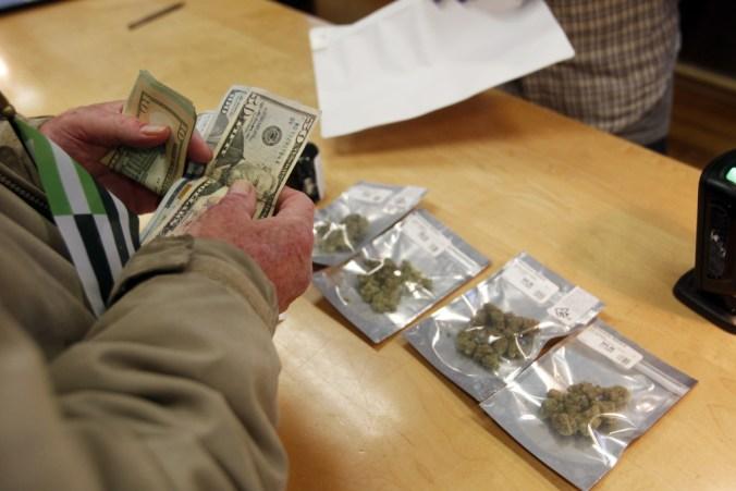 A customer purchases marijuana at Harborside marijuana dispensary, Monday, Jan. 1, 2018, in Oakland, Calif.