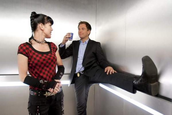 A woman and a man are sharing an elevator.  The woman is standing in the centre of the space, the man is leaning against the corner walls, holding a cup of coffee and streatching out one leg to rest on the elevator hand-rail. He is smiling smugly.