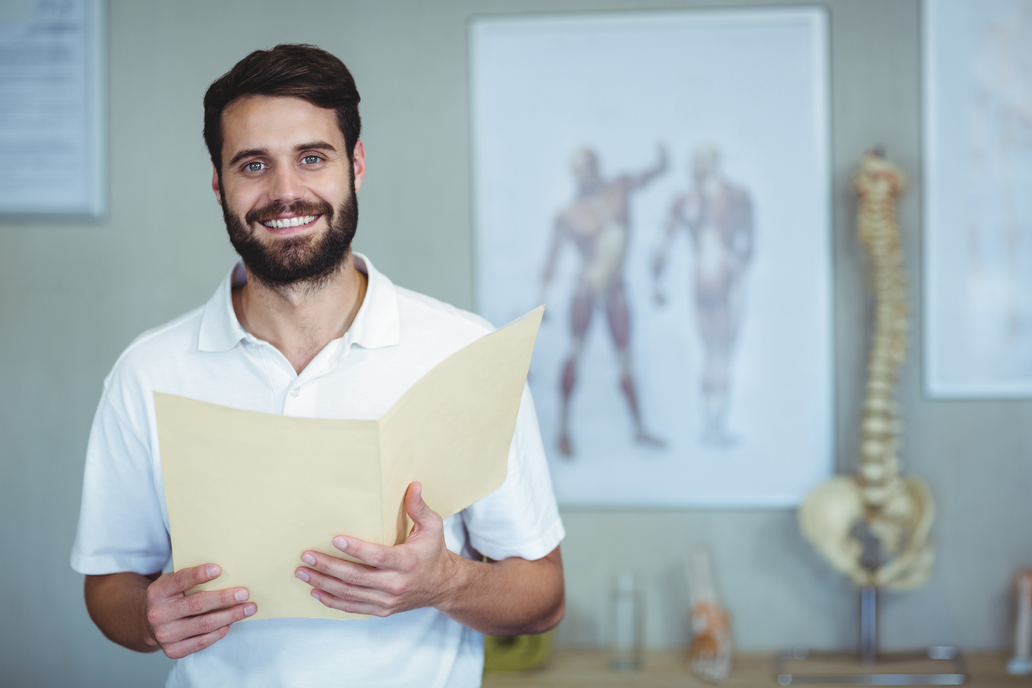 A physical therapist smiling while managing paperwork.