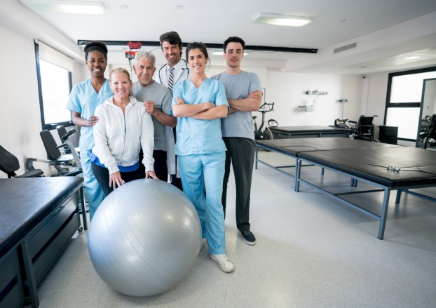 Diverse team of healthcare professionals and patients at a physical rehabilitation clinic all looking at camera smiling with arms crossed