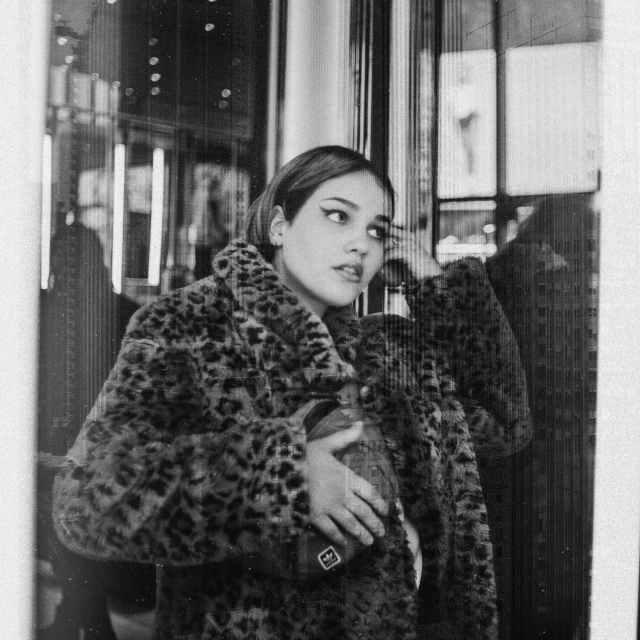 trendy young woman standing near glass door on street