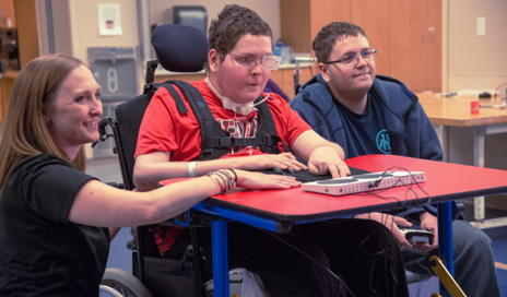 Erin Muston-Firsch, MSOT, looks on as Corey uses features built into the new adaptive controller to play video games with his twin brother, Zachary.