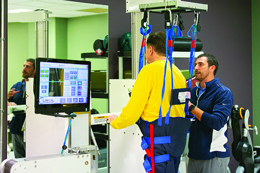 Under therapist supervision, Greg Myers uses a treadmill device that places him in a standing position as robotics assist his legs to walk on a treadmill. Sensors continuously monitor walking patterns, changing power and speed according to Myers's mobility.