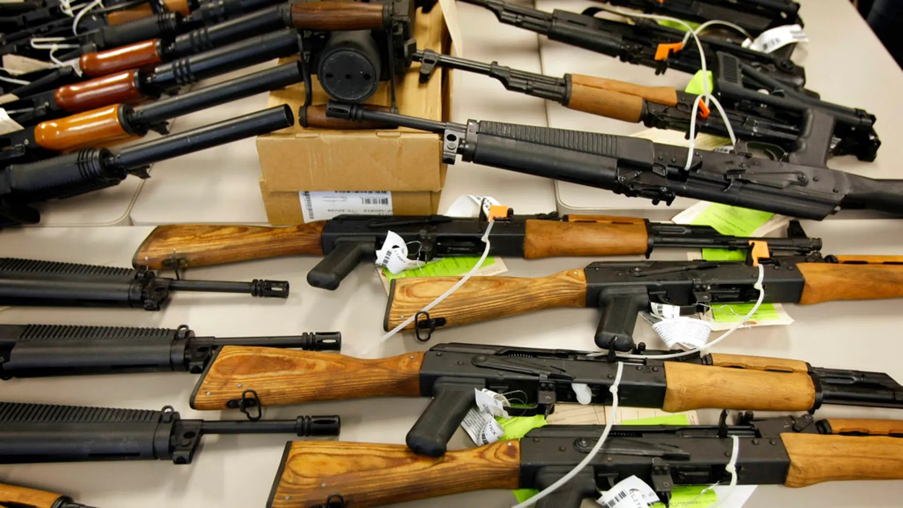 A cache of weapons seized by law enforcement that were to be smuggled into Mexico is displayed in Phoenix.