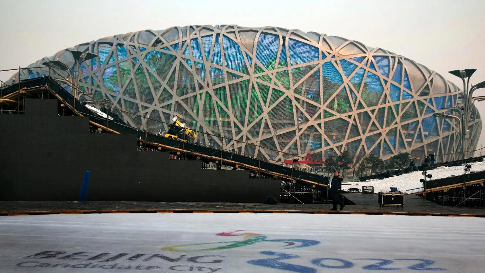 """FOR STORY OLYMPICS 2022 BID - FILE - In this Dec. 26, 2014 file photo, a worker walks past an ice rink with the logo for Beijing's Winter Olympics bid ahead of a countdown event to the new year in front of the iconic Beijing National Stadium """"Bird's Nest"""" in Beijing. (AP Photo/Ng Han Guan, File)"""