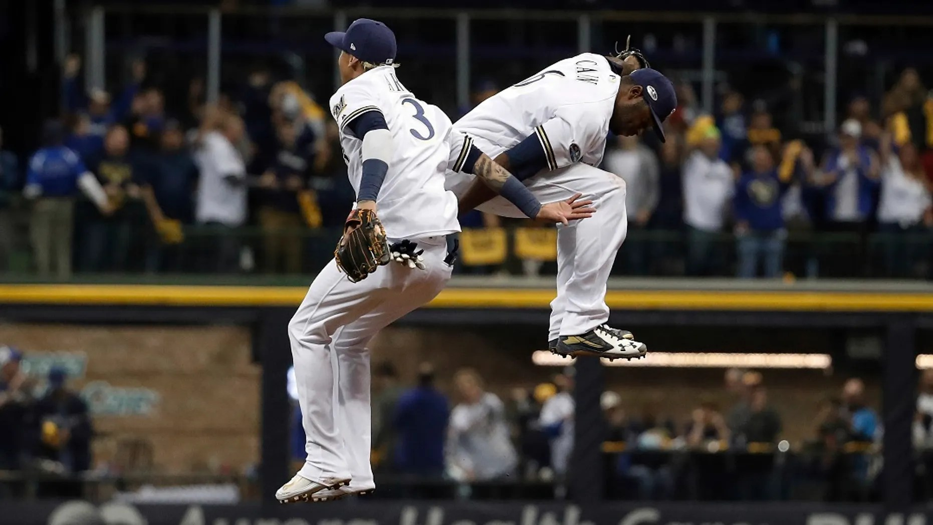 file - Milwaukee Brewers' Orlando Arcia (3) and Lorenzo Cain (6) celebrate after Game 6 of the National League Championship Series baseball game against the Los Angeles Dodgers.