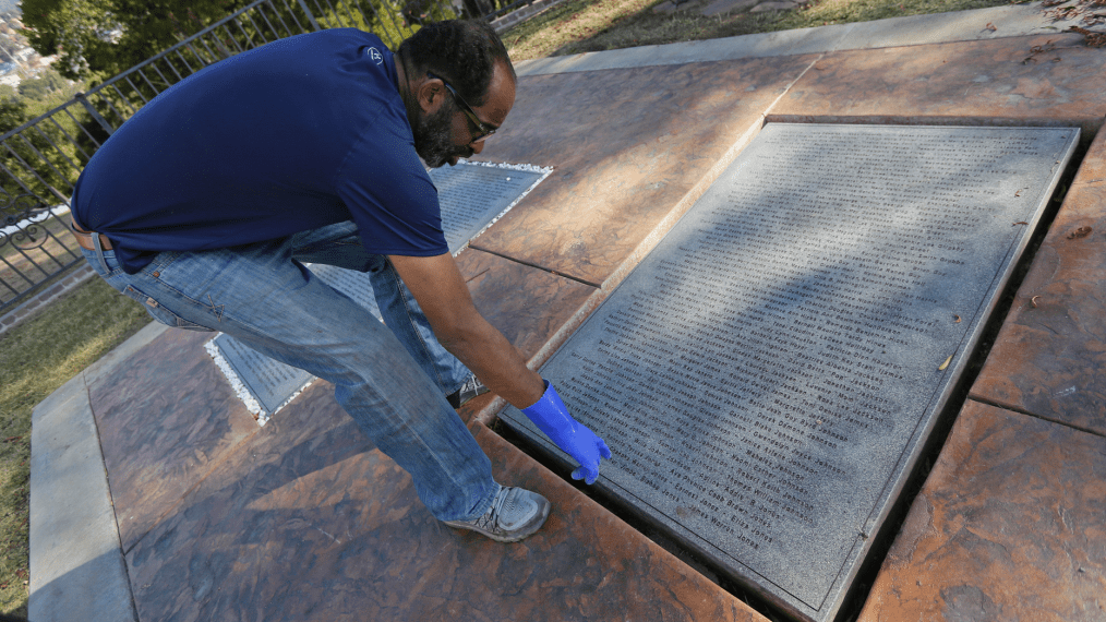 In this Thursday, Oct. 25, 2018, photo, Jim Jones Jr. points to the names of family members on the Jonestown victim memorial in the Evergreen Cemetery in Oakland, Calif. Ceremonies were held at the cemetery to mark the mass murders and suicides 40 years earlier of more than 900 Americans orchestrated by the Rev. Jim Jones at a jungle settlement in Guyana, South America. The unclaimed or unidentified remains of more than 400 victims of the Jonestown tragedy on Nov. 18, 1978, are buried at the cemetery. (AP Photo/Eric Risberg)
