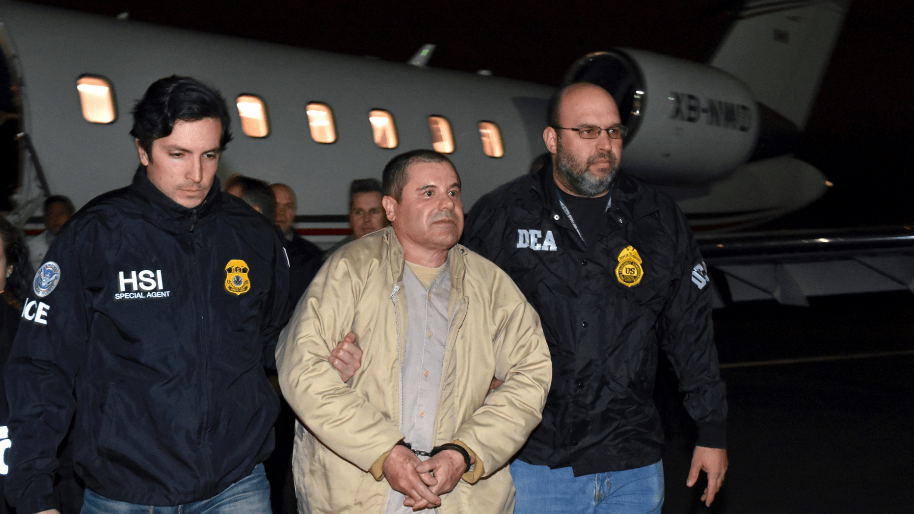 """In this Jan. 19, 2017, file photo provided U.S. law enforcement, authorities escort Joaquin """"El Chapo"""" Guzman, center, from a plane to a waiting caravan of SUVs at Long Island MacArthur Airport, in Ronkonkoma, New York."""