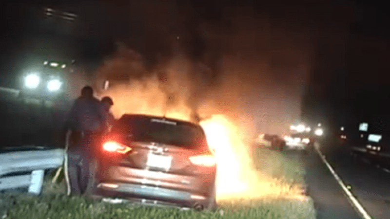 Two New Jersey State Police troopers rescue an unconscious motorist from a burning car.