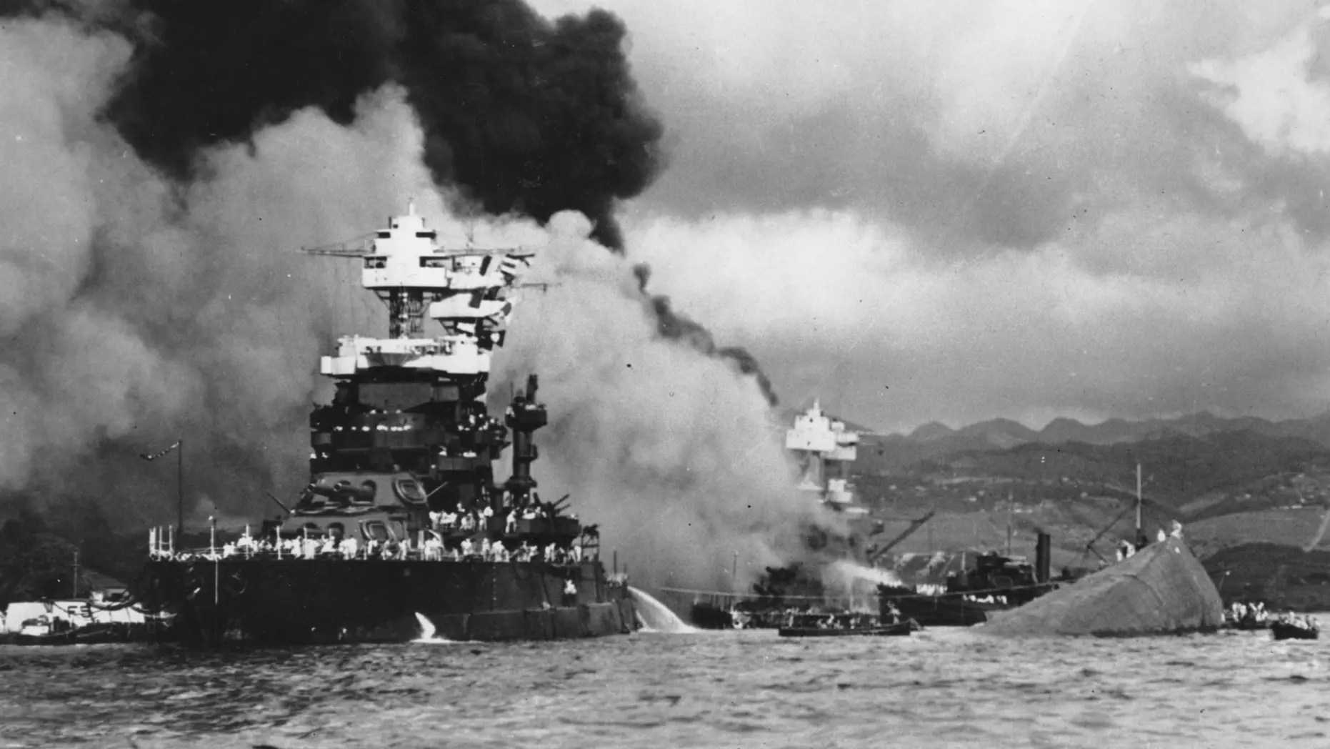 In this Dec. 7, 1941 file photo, part of the hull of the capsized USS Oklahoma is seen at right as the battleship USS West Virginia, center, begins to sink after suffering heavy damage, while the USS Maryland, left, is still afloat in Pearl Harbor, Oahu, Hawaii.