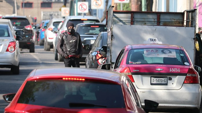 A motorcyclist pauses waiting for fuel in Mexico City