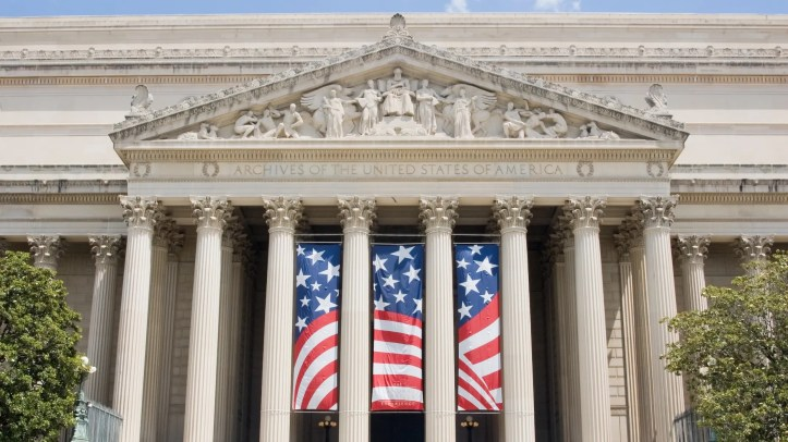 United States National Archives in Washington, DC with a huge flag hanging on its columns.