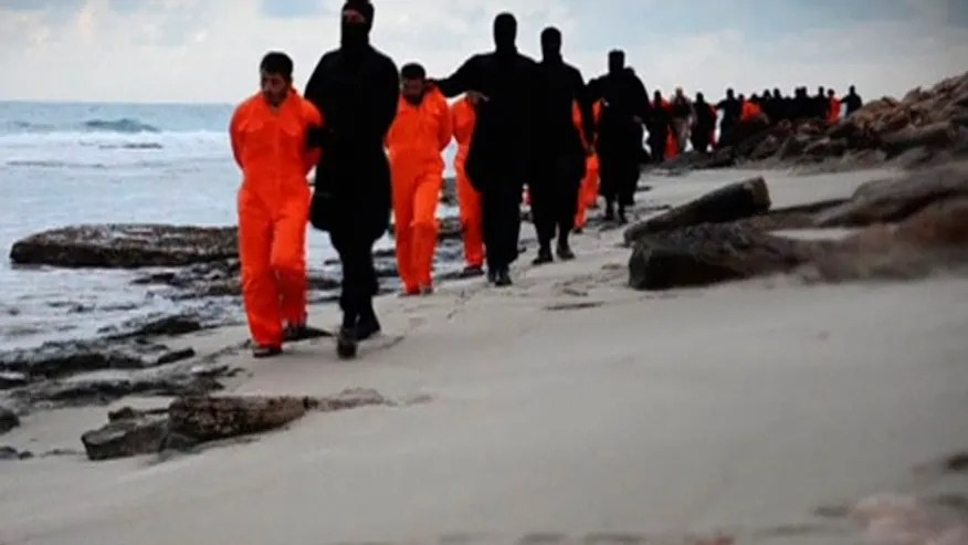 <div class=__reading__mode__extracted__imagecaption>Feb. 15, 2015: Men in orange jumpsuits purported to be Egyptian Christians held captive by the Islamic State (IS) are marched by armed men along a beach.
