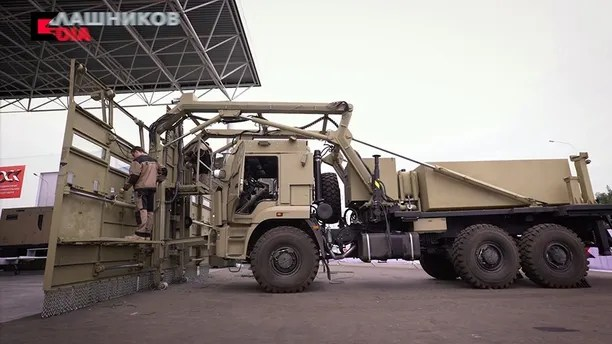 In this photo provided by the Kalashnikov company and made available on Tuesday, Aug. 29 2017, Russia's Kalashnikov company, the maker of the prolific assault rifle, present a formidable crowd control vehicle in Moscow on Friday, Aug. 23, 2017. The Shchit (Shield) vehicle is based on a heavy truck with a broad list of metal attached to its front. It is also equipped with a water cannon and offers protected positions for police officers. (Kalashnikov Company via AP)