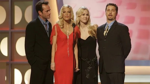 """The cast of the hit television series """"Beverly Hills 90210 (L-R) Luke Perry, Tori Spelling, Jennie Garth and Jason Priestley pay tribute to producer Aaron Spelling, the most prolific producer of television programming in history, prior to presenting Spelling with the Pioneer award at the 3rd annual TV Land Awards in Santa Monica, California March 13, 2005. Spelling created such shows as """"Dynasty,"""" """"Beverly Hills 90210,"""" """"The Mod Squad"""" and """"7th Heaven."""" The awards show honors classic television shows and performers. The 3rd annual TV Land Awards will be telecast in the United States on the TV Land cable channel March 16. REUTERS/Fred Prouser  FSP - RP6DRMRSGGAC"""