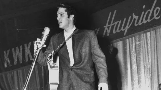 FILE - In this Dec. 15, 1956 file photo, Rock-n-Roll legend Elvis Presley entertains a packed house as a headlining act during a special performance of the KWKH Louisiana Hayride at Hirsch Coliseum in Shreveport, La. A home once owned by Presley in the 1950s as he was skyrocketing to fame was damaged by fire Saturday, April 22, 2017. The Commercial Appeal says Rhodes College looks after the house, now owned by music industry veteran and philanthropist Mike Curb. (Langston McEachern/The Shreveport Times via AP)