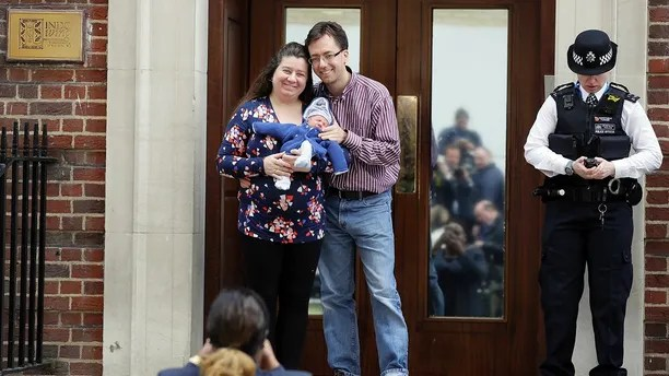 A couple pose for a photo with their newborn baby as they leave the Lindo wing at St Mary's Hospital in London London, Monday, April 23, 2018. Kensington Palace says the Duchess of Cambridge has given birth to her third child, a boy weighing 8 pounds, 7 ounces (3.8 kilograms). (AP Photo/Kirsty Wigglesworth)