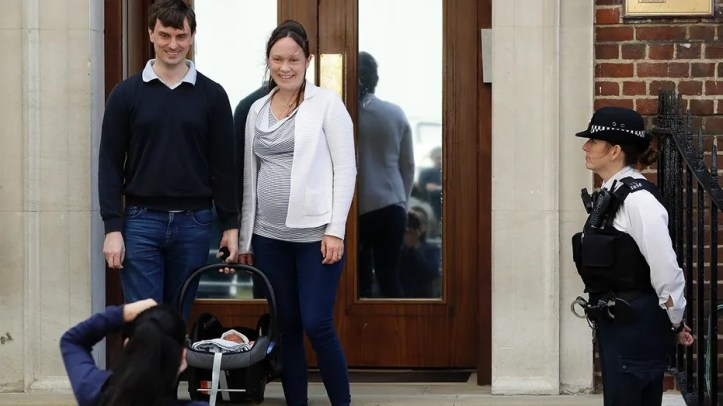 A couple pose for a photo with their newborn baby as they leave the Lindo wing at St Mary's Hospital in London London, Monday, April 23, 2018. Kensington Palace says Prince William's wife, the Duchess of Cambridge has entered a London hospital to give birth to the couple's third child. (AP Photo/Kirsty Wigglesworth)