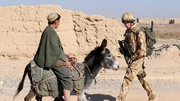 Britain's Prince Harry passes a donkey while on patrol through the deserted town of Garmisir, in Helmand province, southern Afghanistan January 2, 2008. The government is reviewing Prince Harry's presence in Afghanistan, where he has been deployed with the army for 2-1/2 months, following leaks in the international media that he was deployed there, the Defence Ministry said on February 28, 2008. Photograph taken January 2, 2008.     REUTERS/John Stillwell/Pool   (AFGHANISTAN) - GM1E42T0BCG01