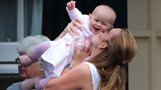 Peter Phillips' wife Autumn kisses their daughter Savannah as they leave Holyrood Palace after the marriage on Saturday between Britain's Zara Phillips, the eldest granddaughter of Queen Elizabeth, and England rugby captain Mike Tindall, in Edinburgh, Scotland July 31, 2011. REUTERS/David Moir  (BRITAIN - Tags: ROYALS ENTERTAINMENT SOCIETY SPORT) - LM1E77V18N201