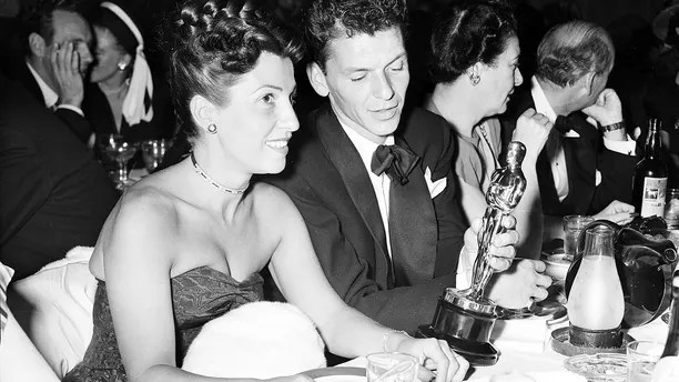 """FILE - In this March 11, 1946 file photo, at a crowded table at Ciro's, Frank Sinatra steals a glance at his Oscar which he won for his performance in the film """"The House I Live In,"""" as his wife Nancy looks on at left. Nancy Sinatra Sr., the childhood sweetheart of Frank Sinatra who became the first of his four wives and the mother of his three children, has died. She was 101. Her daughter, Nancy Sinatra Jr., tweeted that her mother died Friday, July 13, 2018.  (AP Photo/File)"""