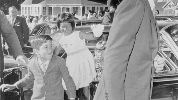 President John F. Kennedy arrives for a 9:00 A.M. Mass at St. Francis Xavier Catholic Church in Hyannis. Following their uncle to the service are (left to right) Christopher Lawford, Maria Shriver, and Sydney Lawford.