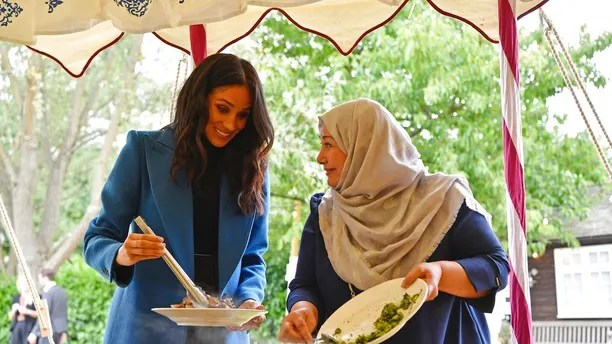 Meghan, the Duchess of Sussex, left, reacts with one of the women behind the cookbook