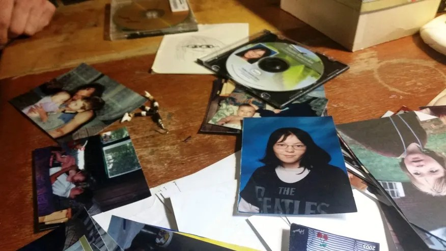 FILE - In this Nov. 16, 2016 file photo, photographs of Charles Knowles, the transgender son of Michelle Knowles, lie scattered on a table in her home in North Vassalboro, Maine. Juvenile detention and correctional facilities nationwide are struggling with how to house and treat transgender youth, who face disproportionate incarceration rates. Charles Knowles, 16, killed himself while temporarily detained at Long Creek Youth Development Center on Nov. 1, in South Portland, Maine. (AP Photo/Marina Villeneuve, File)