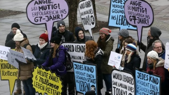 Activists hold banners to support global vaccination near the venues of the GAVI conference in Berlin