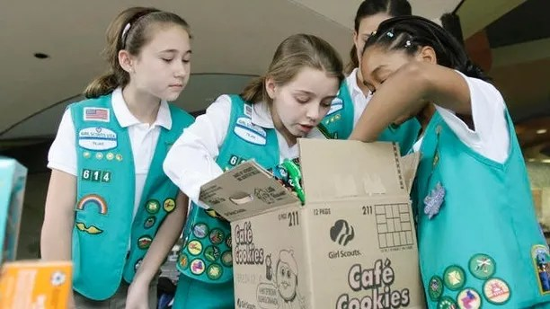 Girl Scouts Caroline Jahr, 11, from left, Audrey Figari, 12, and Angelica Armstrong, 10, sort through a case of Girl Scout cookies,  Friday, Feb. 23, 2007, in Dallas. The Girl Scouts have marked their 90th year in the cookie business by getting most of the artificial fat out of all varieties of their iconic treats, which had been under attack by a few health-focused consumer groups. (AP Photo/Matt Slocum)