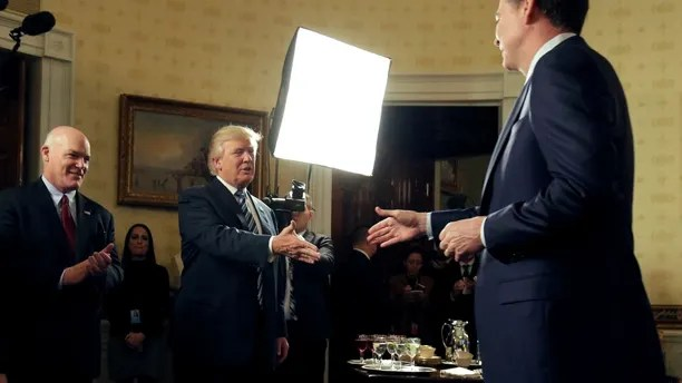 U.S. President Donald Trump greets Director of the FBI James Comey as Director of the Secret Service Joseph Clancy (L) watches during the Inaugural Law Enforcement Officers and First Responders Reception in the Blue Room of the White House in Washington, U.S., January 22, 2017.      REUTERS/Joshua Roberts - RTSWV5T