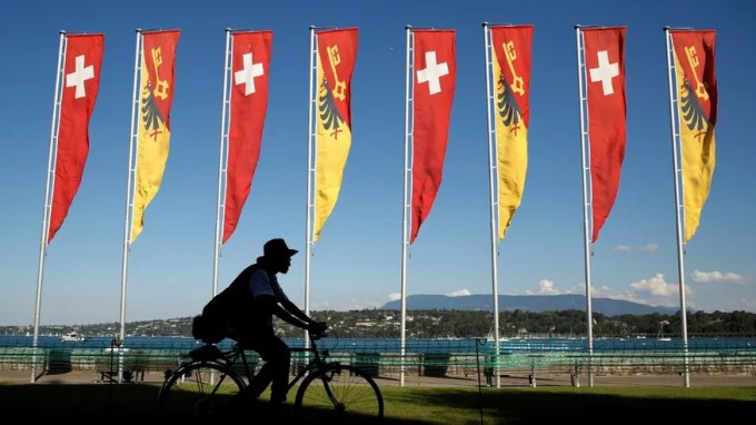 Sept. 9, 2016: A cyclist passes flags of Switzerland and the Canton of Geneva along the shore of Lake Geneva on a warm and sunny day in Switzerland.