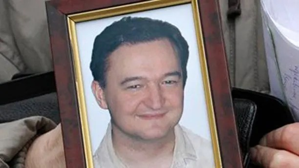 FILE - This is a  Monday, Nov. 30, 2009 file photo showing a portrait of lawyer Sergei Magnitsky who died in jail, as it is held  by his mother Nataliya Magnitskaya,  as she speaks during an exclusive interview with the AP in Moscow, Russia, Monday, Nov. 30, 2009. Activists plan to present evidence Tuesday, July 5, 2011, that a Russian lawyer who accused officials of corruption died after a brutal beating by prison guards, saying investigators' findings that a lack of medical treatment killed the man fell short of the full truth. (AP Photo/Alexander Zemlianichenko, File)