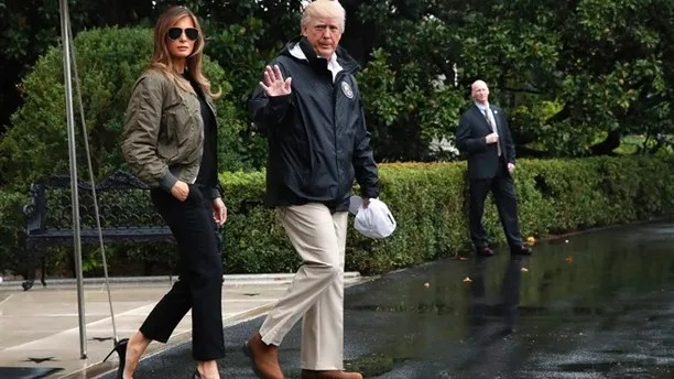 President Donald Trump, accompanied by first lady Melania Trump, waves as they walk from the White House to the South Lawn, Tuesday, Aug. 29, 2017, to board Marine One for a short trip to Andrews Air Force Base, Md.m then onto Texas to view the federal government's response to Harvey's devastating flooding in Texas. (AP Photo/Jacquelyn Martin)