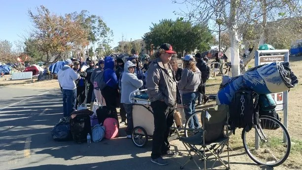 Homeless people line up in preparation to move from their homeless camp site along a riverbed in Anaheim, Calif. on Tuesday, Feb. 20, 2018. Authorities are being allowed to shut down a large homeless encampment in Southern California and move hundreds of tent-dwellers into motel rooms. (AP Photo/Amy Taxin)
