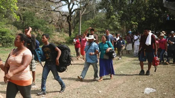 "Central American migrants arrive to a sports center during the annual Migrant Stations of the Cross caravan or ""Via crucis,"" organized by the ""Pueblo Sin Fronteras"" activist group, as the group makes a few-days stop in Matias Romero, Oaxaca state, Mexico, Monday, April 2, 2018.  The organized portions of the caravans usually don't proceed much farther north than the Gulf coast state of Veracruz, while some migrants, moving as individuals or in smaller groups, often take buses or trucks from there to the U.S. border. (AP Photo/Felix Marquez)"