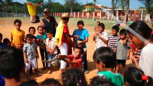 """Central American migrant children play with a piñata during the annual Migrant Stations of the Cross caravan or """"Via Crucis,"""" organized by the """"Pueblo Sin Fronteras"""" activist group, at a sports center as the caravan stops for a few days in Matias Romero, Oaxaca state, Mexico, Monday, April 2, 2018. A Mexican government official said the caravans are tolerated because migrants have a right under Mexican law to request asylum in Mexico or to request a humanitarian visa allowing travel to the U.S. border to seek asylum in the United States. (AP Photo/Felix Marquez)"""