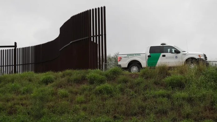 November 13, 2016: A US customs and border patrol agent passes a section of the border wall in Hidalgo, Texas.