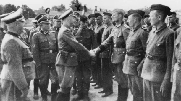 This 1942 photo provided by the the public prosecutor's office in Hamburg via the United States Holocaust Memorial Museum, shows Heinrich Himmler, center left, shaking hands with new guard recruits at the Trawniki concentration camp in Nazi occupied Poland. Trawniki is the same camp, where some time after this photo was made, Jakiw Palij trained and served as a guard.  The White House says that Palij, a 95-year-old former Nazi concentration camp guard has been deported to Germany, 14 years after a judge ordered his expulsion. (public prosecutor's office in Hamburg via the United States Holocaust Memorial Museum via AP)